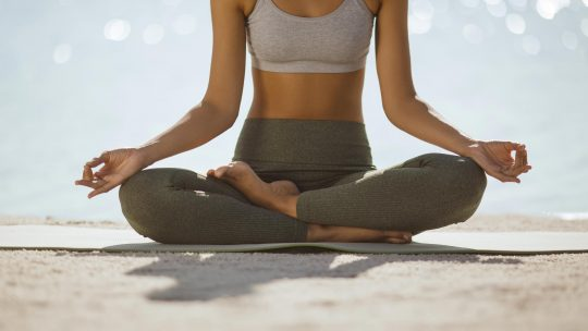 woman-close-up-in-yoga-meditation-pose-on-nature-4VDXEDK