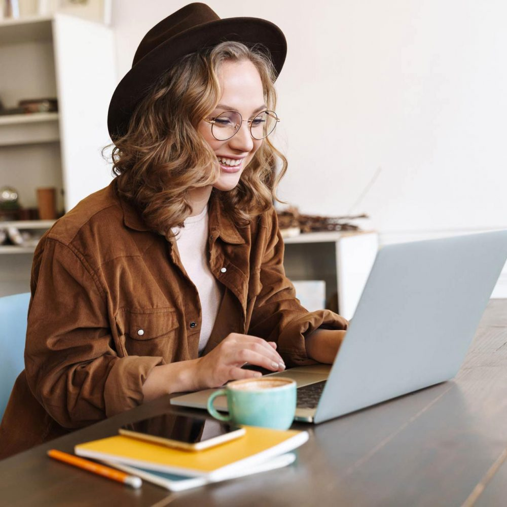 image-of-cheerful-woman-working-with-laptop-while--CNX4RJP
