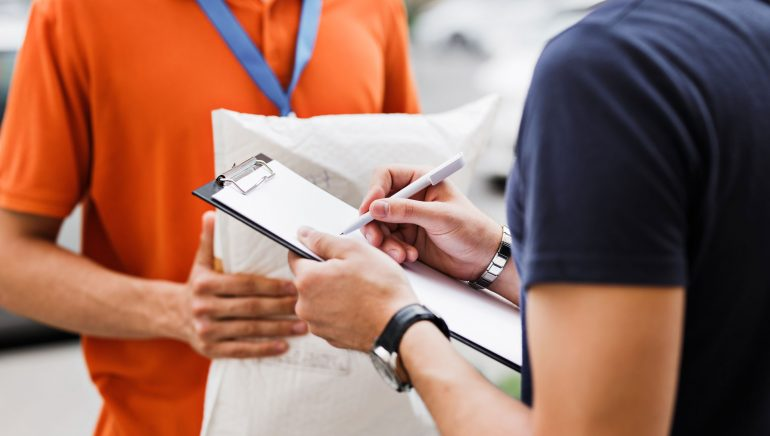 A person wearing an orange T-shirt and a name tag is delivering a parcel to a client, who is putting his signature on the receipt. Friendly worker, high quality delivery service.
