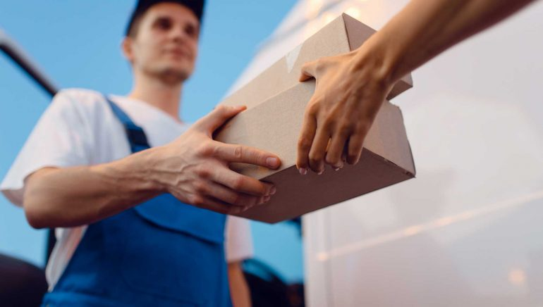 Deliveryman in uniform gives parcel to female recipient at the car, delivery service. Man holding cardboard package near the vehicle, male deliver and woman, courier or shipping job