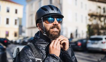 Male hipster courier putting on a helmet in city, delivering packages. Copy space.