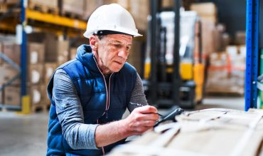 Portrait of a senior male warehouse worker or a supervisor with handheld barcode scanner.