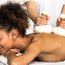African-american woman enjoying Thai herb massage, relaxing in spa, panorama